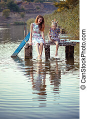 Mother and daughter sitting on the pier - Happy family -...
