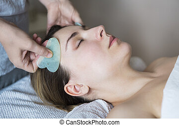 Young woman have face treatment at beauty clinic