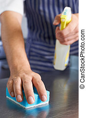 Close Up Of Worker In Restaurant Kitchen Cleaning Down After...