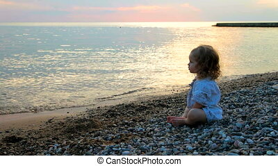 little girl on the sunset beach - A little girl sitting on...