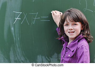 happy school girl on math classes finding solution and...
