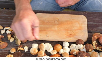 Cleaning of wild mushroom with kitchen knife in old hands....