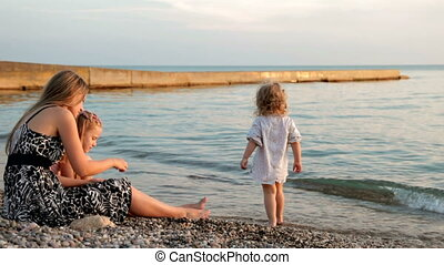 family at sunset - mother with two daughters at the beach...