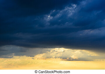 Dark clouds overlook a beautiful and warm sunset - After a...