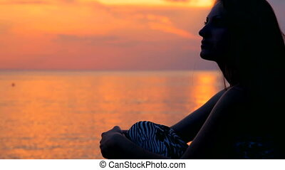 woman watching sunset - young woman watching sunset at the...