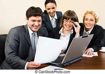 Working in a group - Group of four smiling businesspeople...