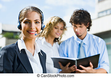 Working together - Portrait of smiling woman with headset on...
