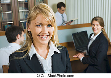 Young beautiful smiling woman in a working environment on a background of her business team