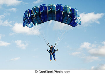 The girl  parachutist in dark blue overalls