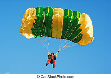 The guy parachutist in red overalls under a yellow-green...