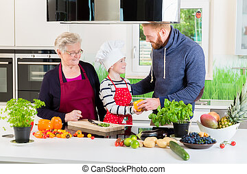 Dad, grandma and kid cooking together in kitchen