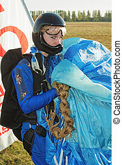 The girl parachutist in dark blue overalls and a black...