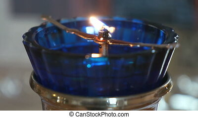 Church oil lamp with a burning candle in temple - Church oil...