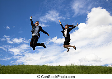 Happy Businessman and businesswoman jumping on a green...