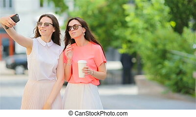 Two young girls taking selfie with smart phone outdoors. Two women after shopping with coffee using smartphone