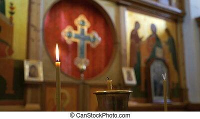 Burning candle on the background Iconostasis