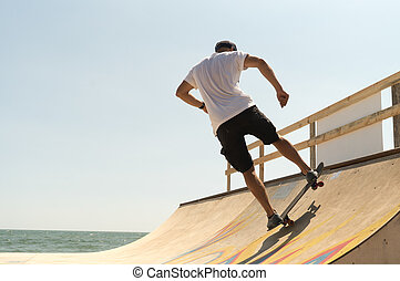 guy skateboarder riding a ramp - guy skateboarder rides on a...