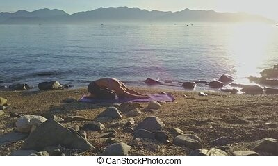 Girl with Ponytail Changes Yoga Poses on Beach in Morning