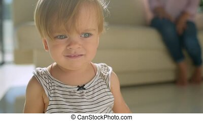 Close up of adorable girl standing in the living room - What...