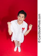 High view of cheerful elegant young handsome asian man over red background.