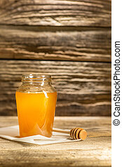 The bowl with honey on wooden table.The bank of honey stay...