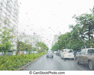 Raindrop on windshield of car driving on the road, blur background.