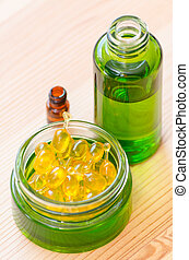 gold capsules of natural cosmetik for face and bottles with essential oils closeup