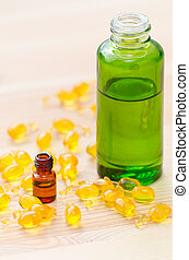 gold capsules of natural cosmetik for face and bottles with essential oils on the wooden