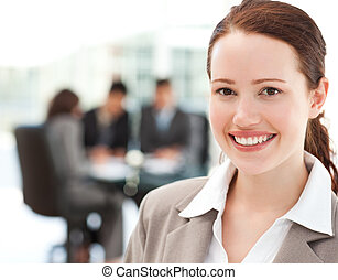 Cheerful businesswoman during a meeting with her team at the...