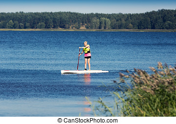 SUP fitness - woman on paddle board in the lake