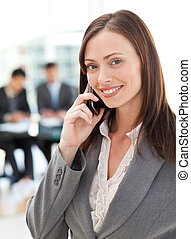 Happy businesswoman on the phone while her team is working