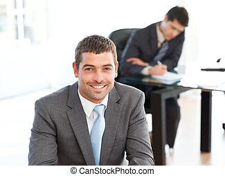Happy businessman in the foreground during a meeting with a...