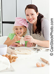 Happy girl with her mother baking little cakes