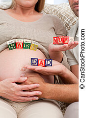 Close up of future parents holding cubes forming the words mom ,dad and baby