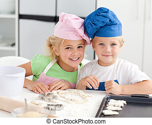 Portrait of two adorable children baking in the kitchen at...