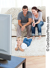 Kid watching television lying on the floor at home