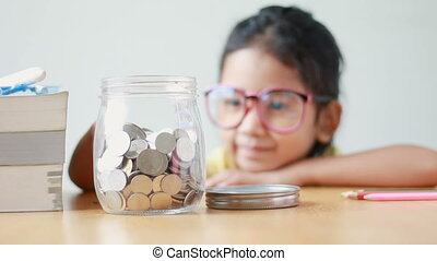 Asian little girl putting the coin into a clear glass jar on...
