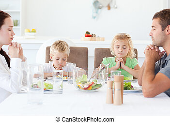 Portrait of a family praying together during the lunch in...