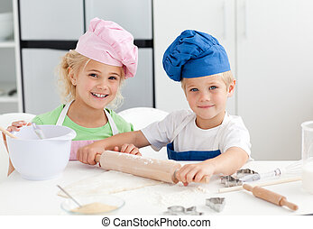 Happy brother and sister preparing a dough standing in the kitchen and looking at the camera