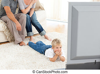 Attentive little boy watching television lying on the floor...