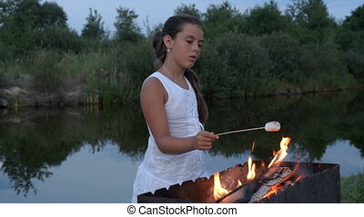 girl fries marshmallows on the fire near the pond - A pretty...