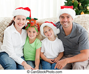 Happy family with Christmas hat looking at the camera and...