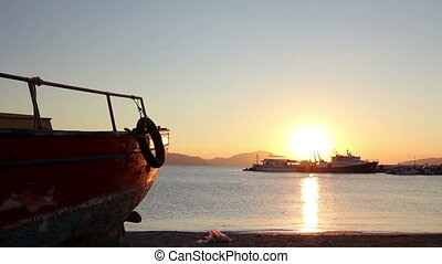 Silhouetted shot of old wooden fishing boat dry docked at...