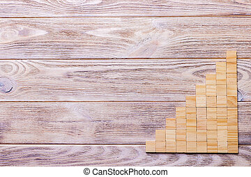 A wooden blocks cube over black wooden textured background with copy space for add word text title. Concept or conceptual Wood block stair or nine steps. Cubic.