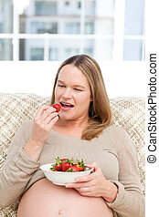 Hungry pregnant woman eating strawberries sitting in the living-room at home