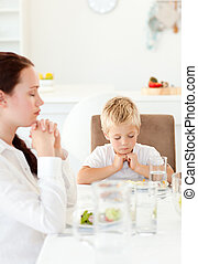 Concentrated little boy praying with his mother before eating their salad in the kitchen