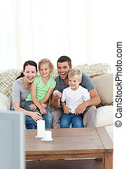 Happy family laughing while watching television sitting on...