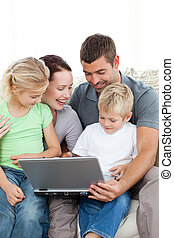 Adorable family working together on a laptop sitting on the sofa in the living-room