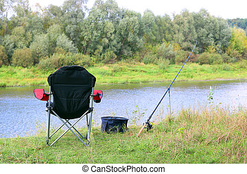 Fishing chair, rod and bait on the river bank in autumn