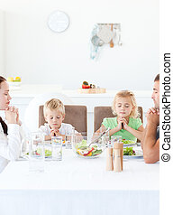 Parents and their children praying during their lunch in the...